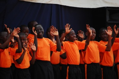 Children's choir singing, smiling and with arms raised
