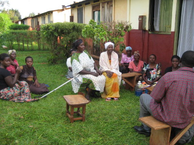 Microfinance group of women talking to Pastor Alfred in front of someone's house.
